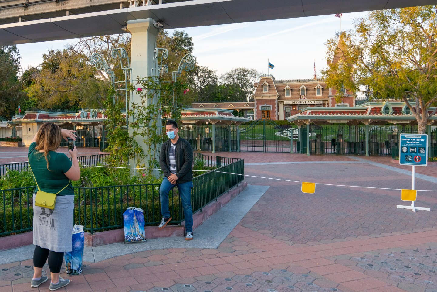 A woman takes a picture of a man outside of the closed Disneyland theme park entrance.