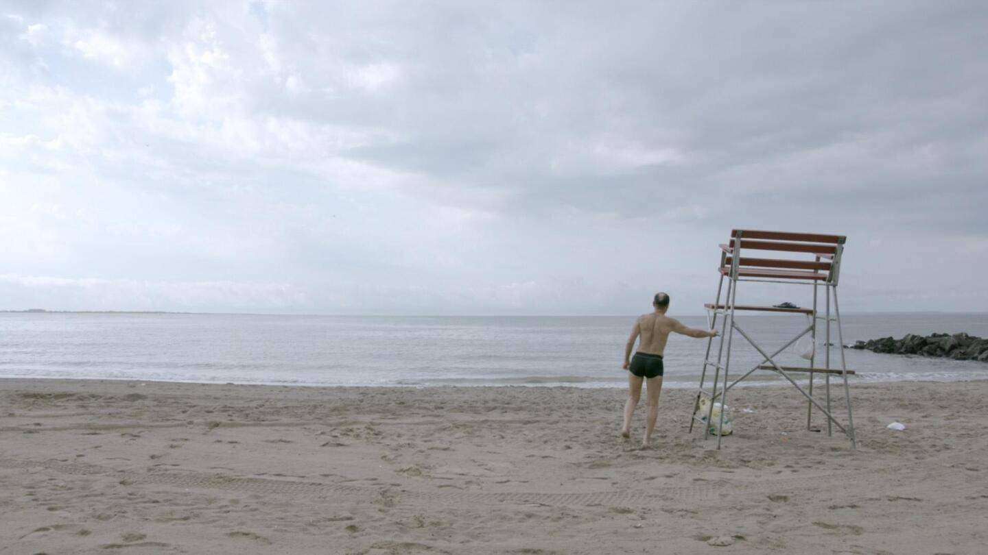 """A man in swimwear at an empty beach faces the ocean. 