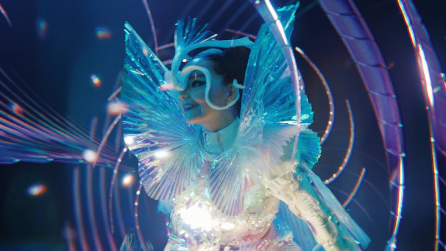 "Still from ""The Gate:"" Bjork has wings and is enveloped by color swirls."