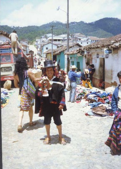 Robert Lopez on a 1980 trip to Guatemala. He's standing in the middle of a cobble-stoned street wearing a black top hat and holding an art piece.