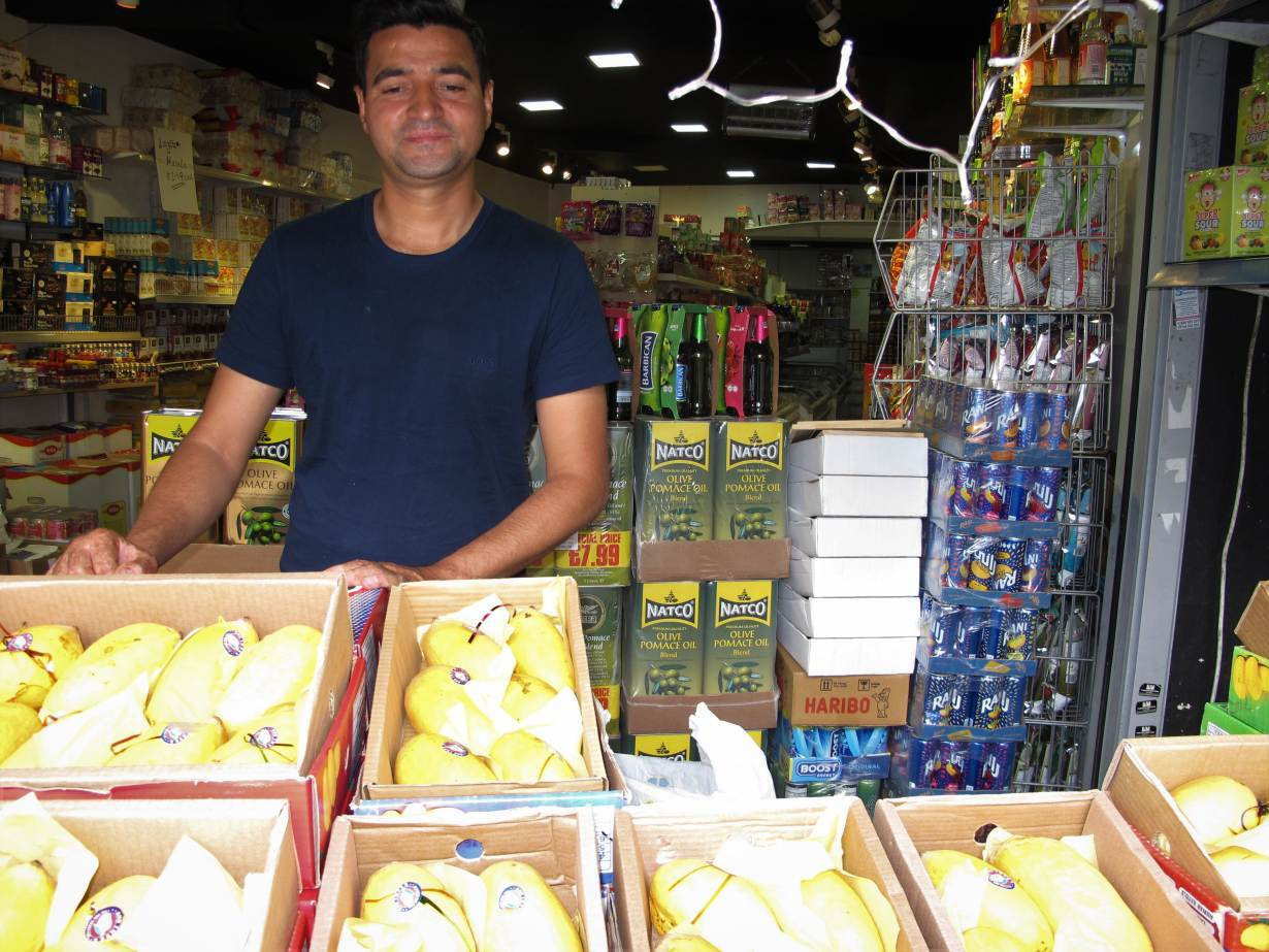 Mango vendor Asif Khaliq stands behind a display of Pakistani and Indian mangoes in the Tooting neighborhood of London, June 15, 2020. | Thomson Reuters Foundation/Laurie Goering