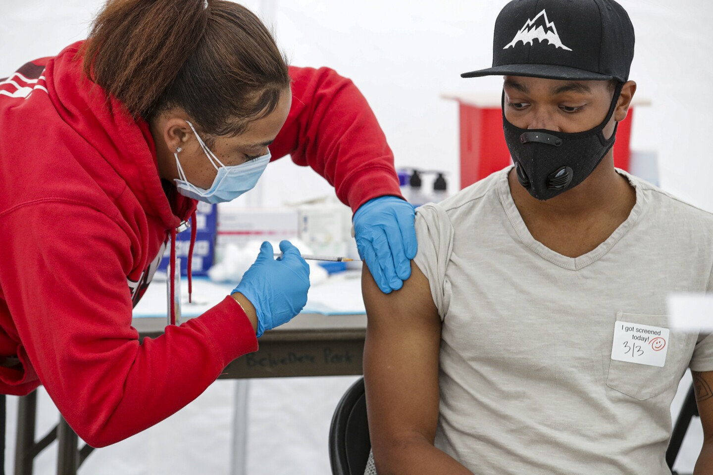 A person in a red sweatshirt administers COVID-19 vaccine to a young Black man. Both are wearing face masks.