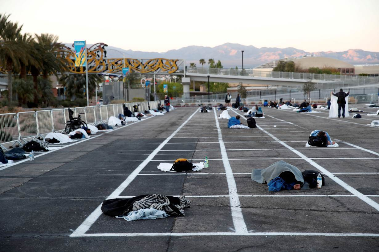 Homeless people sleep in a temporary parking lot shelter at Cashman Center, with spaces marked for social distancing to help slow the spread of coronavirus disease (COVID-19) in Las Vegas, Nevada, U.S. March 30, 2020.