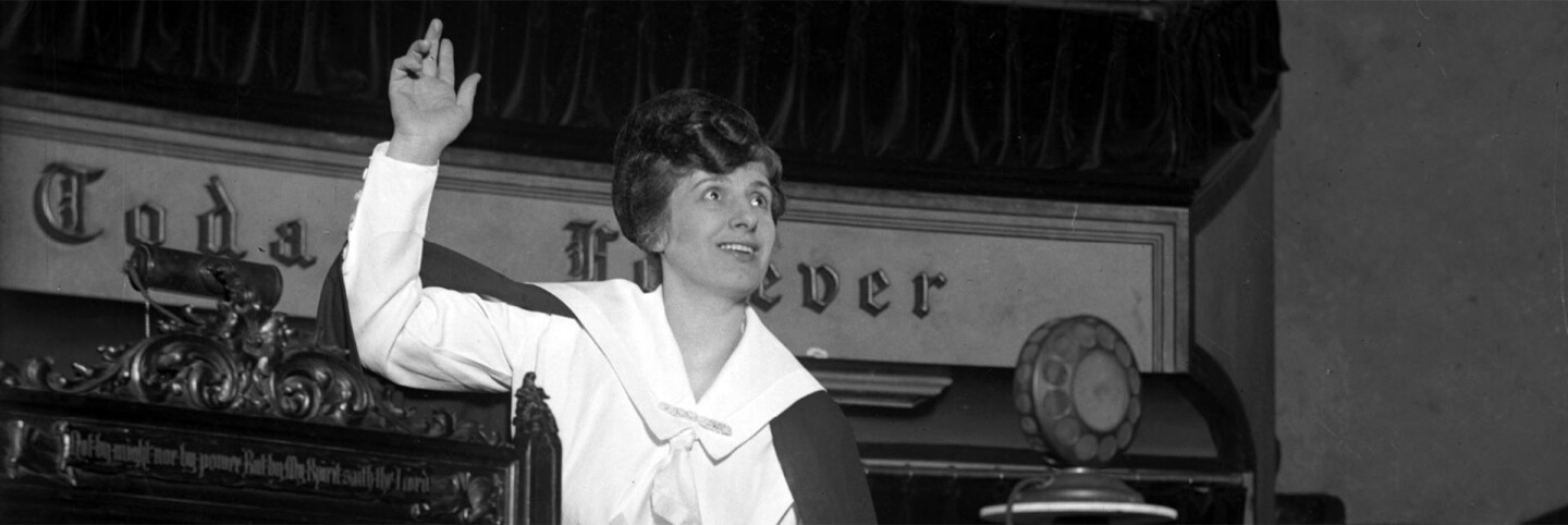 Aimee Semple McPherson preaching in front of a microphone (cropped for header)