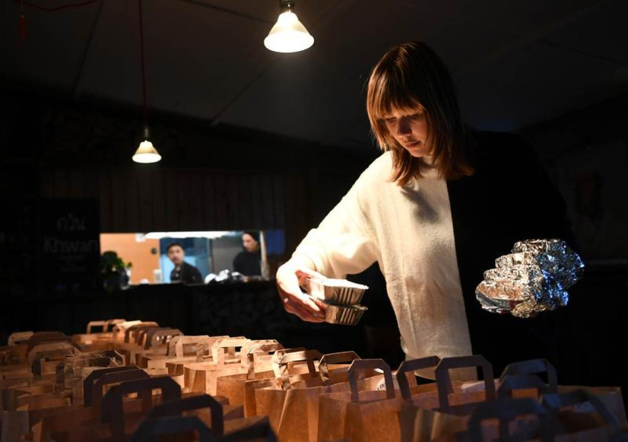 FILE PHOTO: Restaurant staffer Natalie prepares orders for take out and delivery at a restaurant called khwan in district Friedrichshain, Berlin, Germany, March 14, 2020.