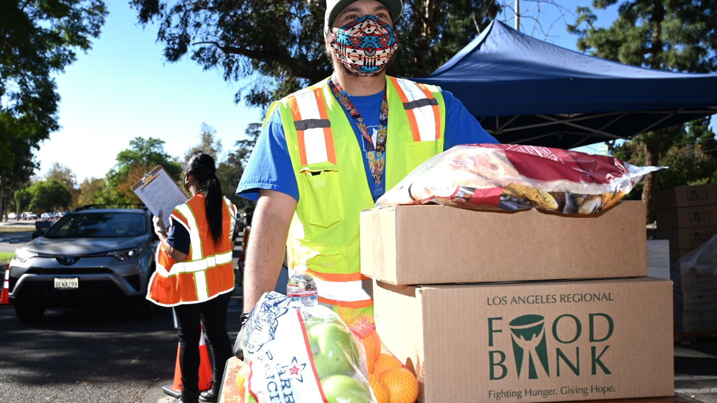 A man in a bright yellow reflective safety vest stands behind two boxes stacked on a table. There are also bags of fruit. The man is wearing a mask and looking off to the distance. Behind him is a person wearing a bright orange safety vest and holding a clipboard. Their back is facing the camera and it appears as if they are guiding a line of cars.