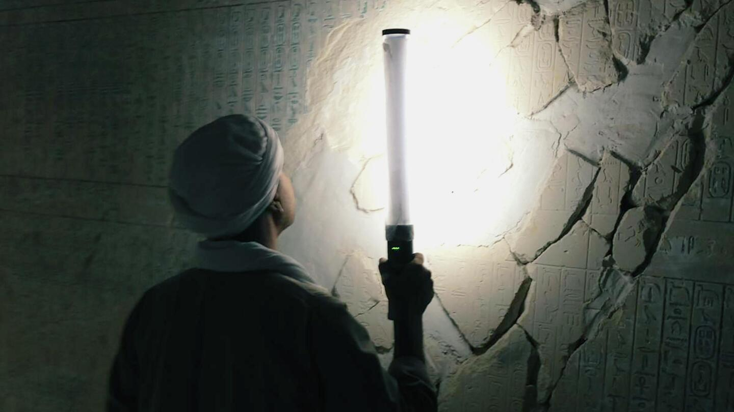 "A man holds a light toward a wall with ancient script carved into it. | ""Secrets of the Dead: Egypt's Darkest Hour"""