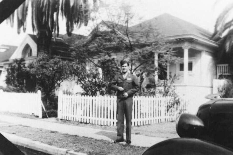 Black and white photo of a Chinese American soldier in uniform standing in front of a house, circa 1940.