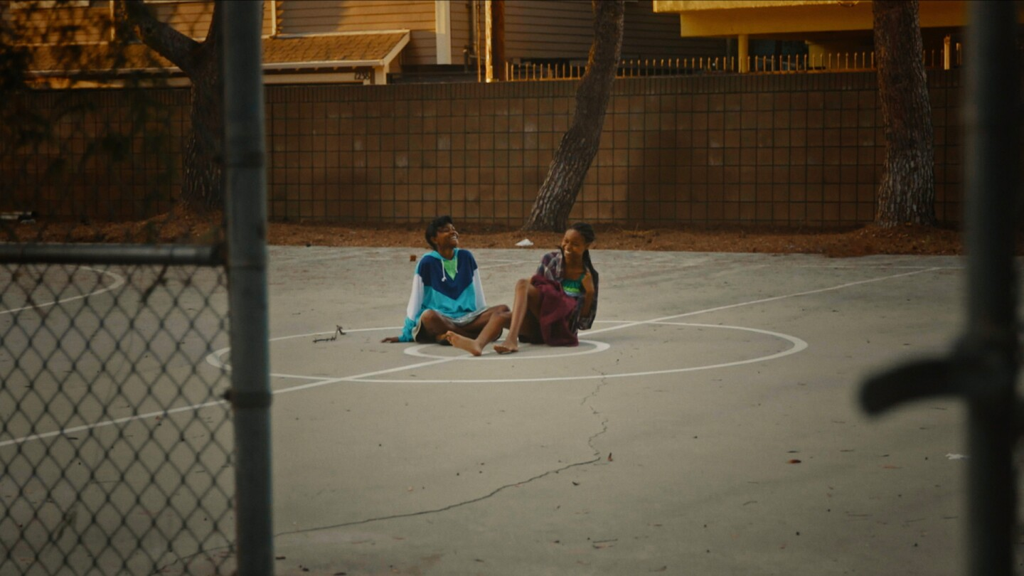 "Two African American young girls talk at a basketball court in a still from ""The Dope Years"" 