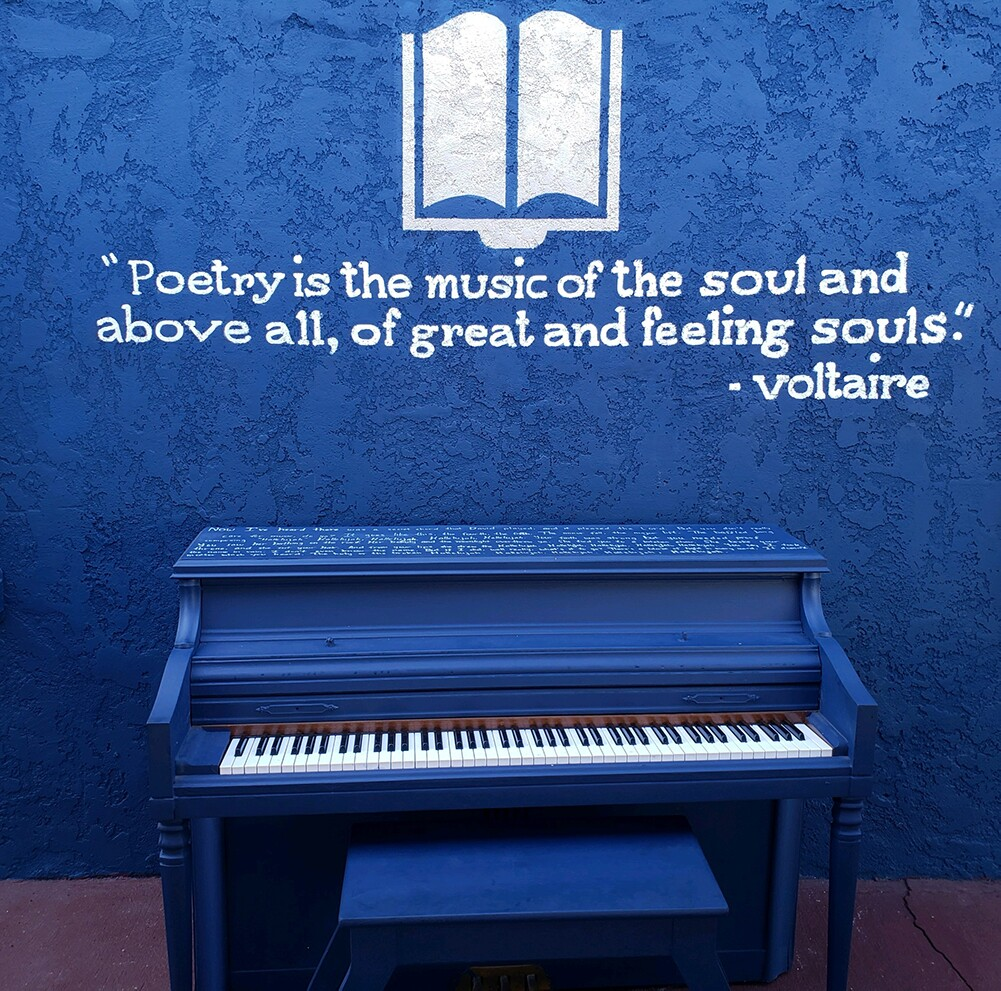 The striking patio at the Sims Library of Poetry features a blue piano with a quote from Voltaire. | Joshua Jones