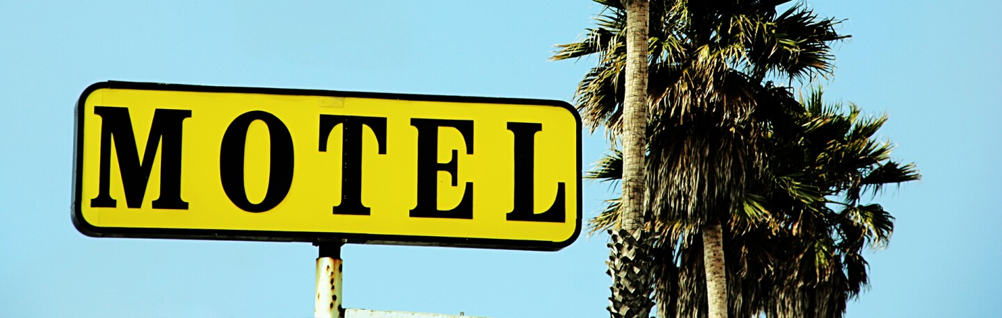 Motel sign with palm trees | Photo: Kevin Russ, iStockPhoto