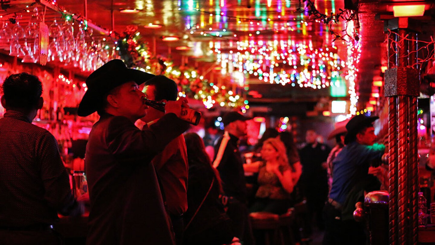 Scene from inside La Cita with men in hats and festive lighting. | Samanta Helou