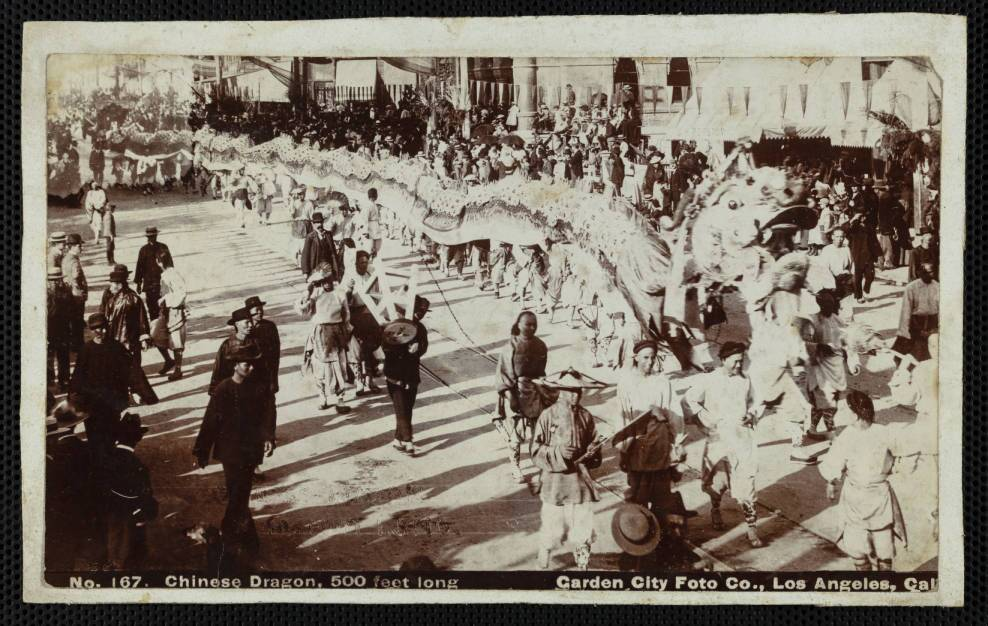 In this cabinet photograph, a few dozen Chinese men walk inside and next to a 500-foot long dragon