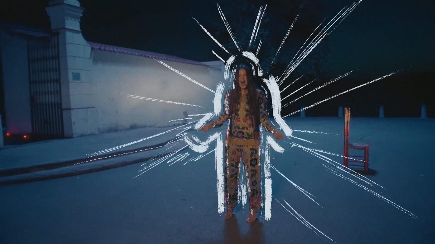 Music video still: Rosalía screams or sings with lines drawn around her
