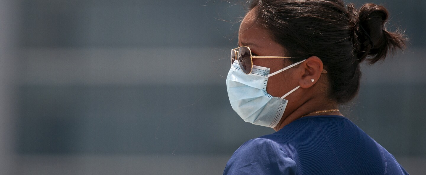 A  medical technician wears a face mask at a drive-thru testing site for COVID-19.