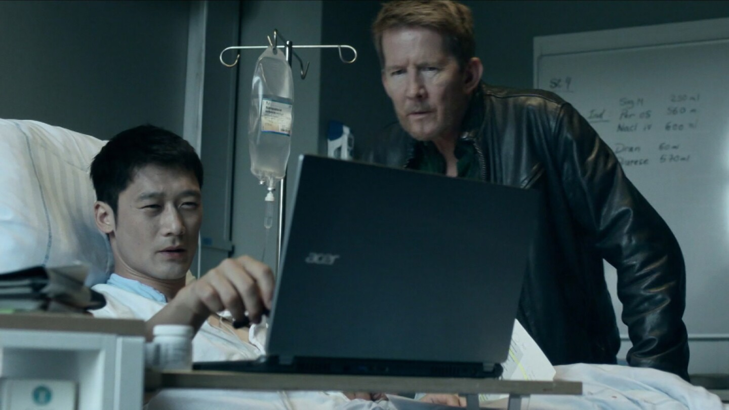 """Alf (left) lies in a hospital bed looking at a computer screen with Mads (right) standing next to him. 