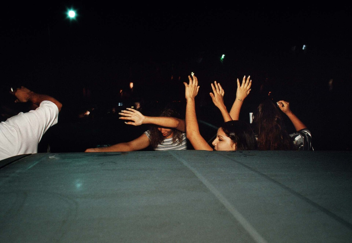 Young people in Pico-Union are photographed with their hands raised behind a car at night.