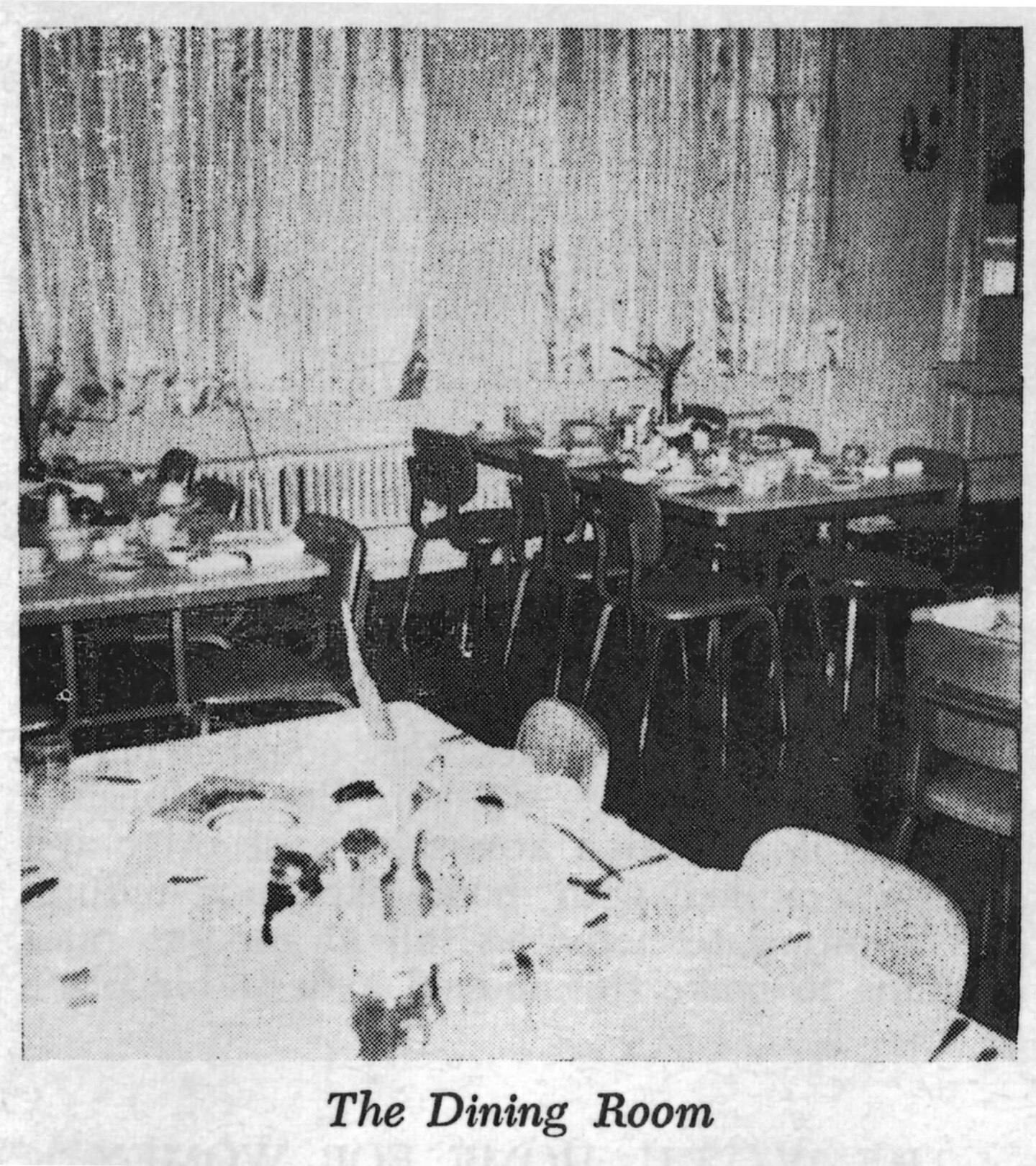 The dining room at the Woman's Christian Temperance Union Home. There are three tables at the table filled with silverware and plates. There are two big windows on the wall with curtains.
