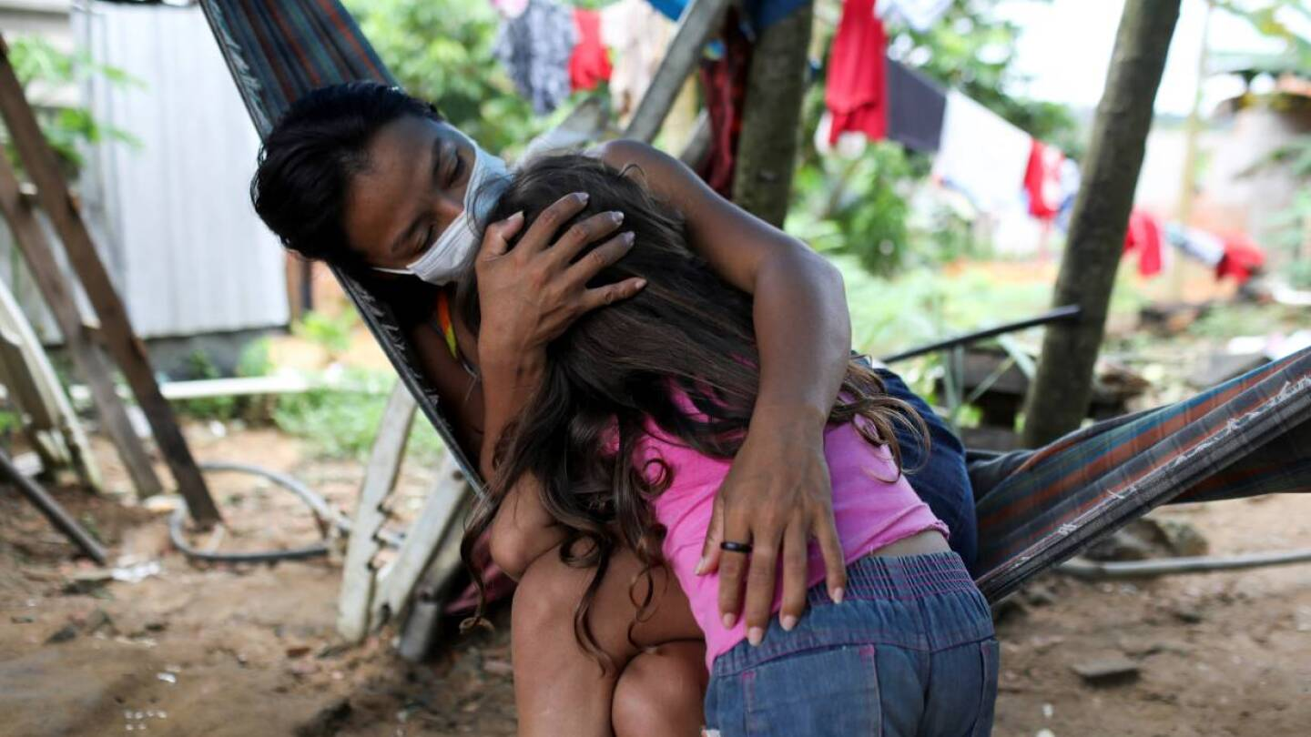 Vanderlecia Ortega dos Santos, 32, a nurse who has volunteered to provide the only frontline care protecting her indigenous community of 700 families from the COVID-19 outbreak, embraces her niece Maria Eduarda Ribeiro Ortega, 4.