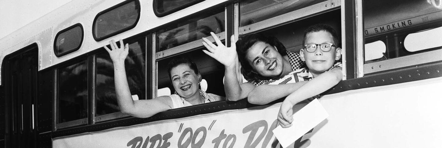 Councilmember Rosalind Wyman (center) waves out of a bus as she introduces a new bus line in 1958 with her constituents. | Los Angeles Examiner/USC Libraries/Corbis via Getty Images