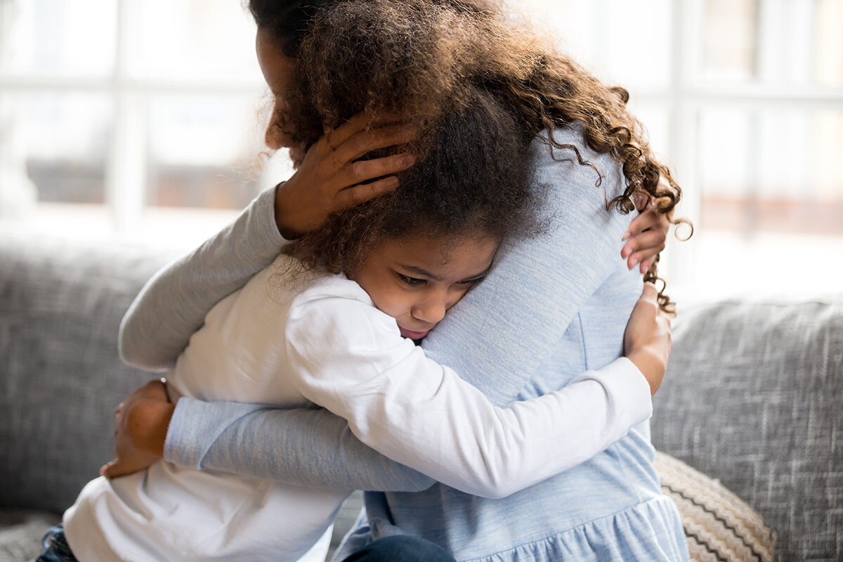 A woman holds a child tightly. | istock