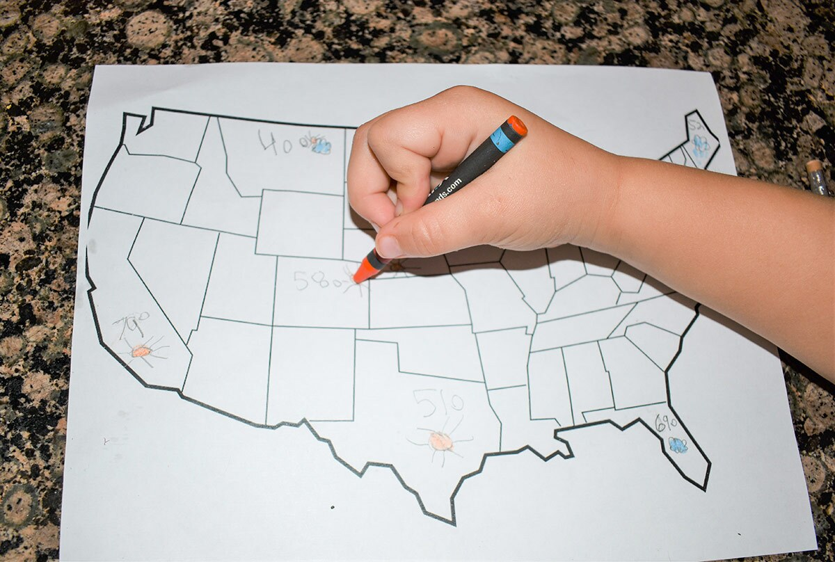A small child's hand draws different temperatures on each state in a map of the United States.