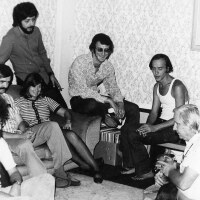 Left to right: John Platonia, Jim Kepner (moustache), Howard Fox (standing), June Herrle, Jim-Ed Thompson, Ralph Schaeffer, Morris Kight, Don Kilhefner (far right) and another person at the Gay Community Services Center, 1971. | Pat Rocco/USC Libraries