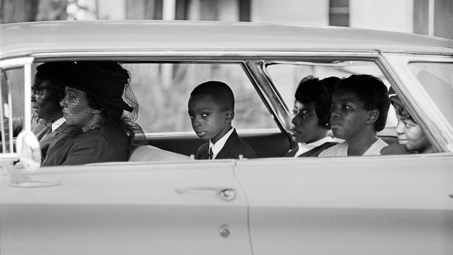 """A group of African Americans sitting in a car, with a boy looking out the window. 