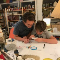 Monica Ramirez Wee's older son goes over the instructions for an arts and craft project with his younger brother.