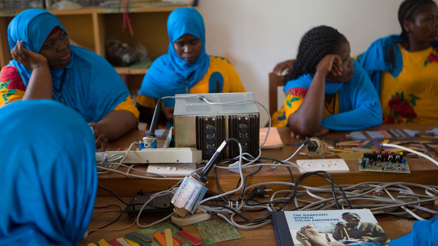 A group of women in Zanzibar sits at a table full of electric eqiupment. | Nicky Milne/Thomson Reuters Foundation