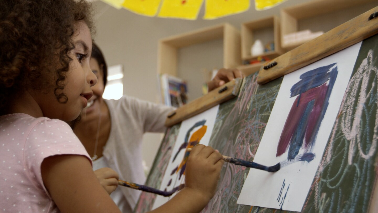 A young girl paints in front of a canvas.