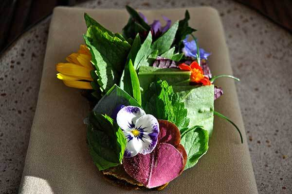 Among the dishes on Willows Inn's menu is the herbed tostado with oyster cream, a dish that includes edible flowers. | Barron Bixler
