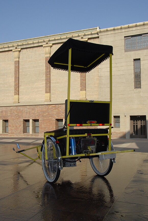 A vehicle, which is as hybrid of a rickshaw and a low-rider, sits outdoors.