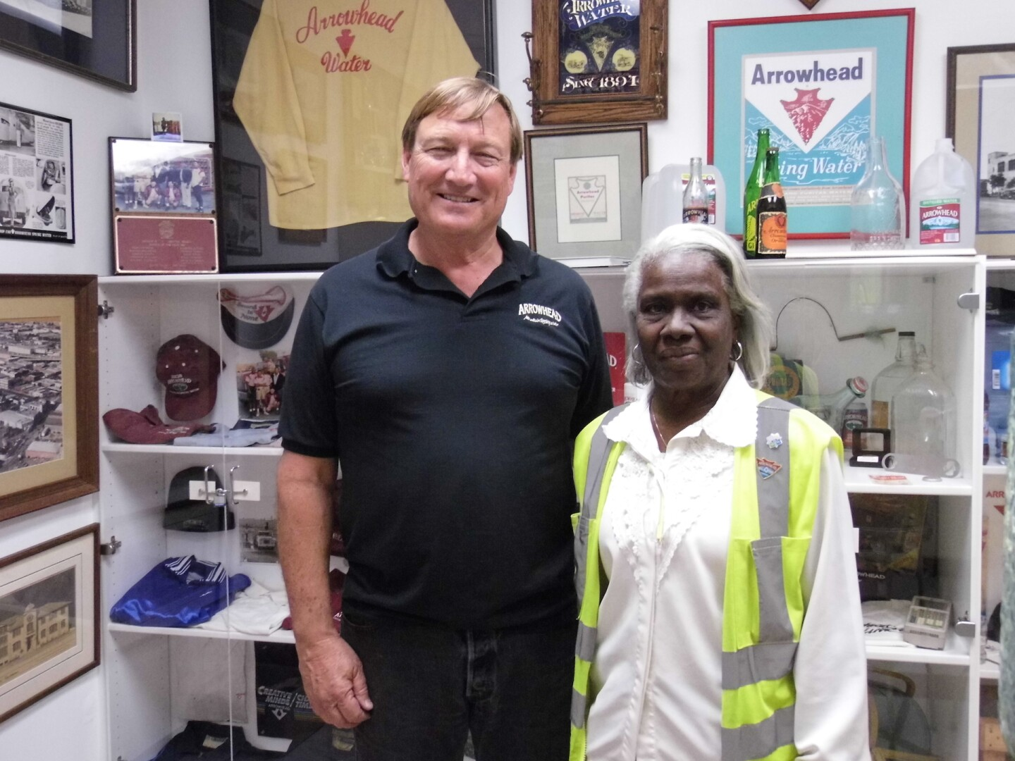 """""""Mrs. G"""" (right) in front of a collection of artifacts from Arrowhead's past"""
