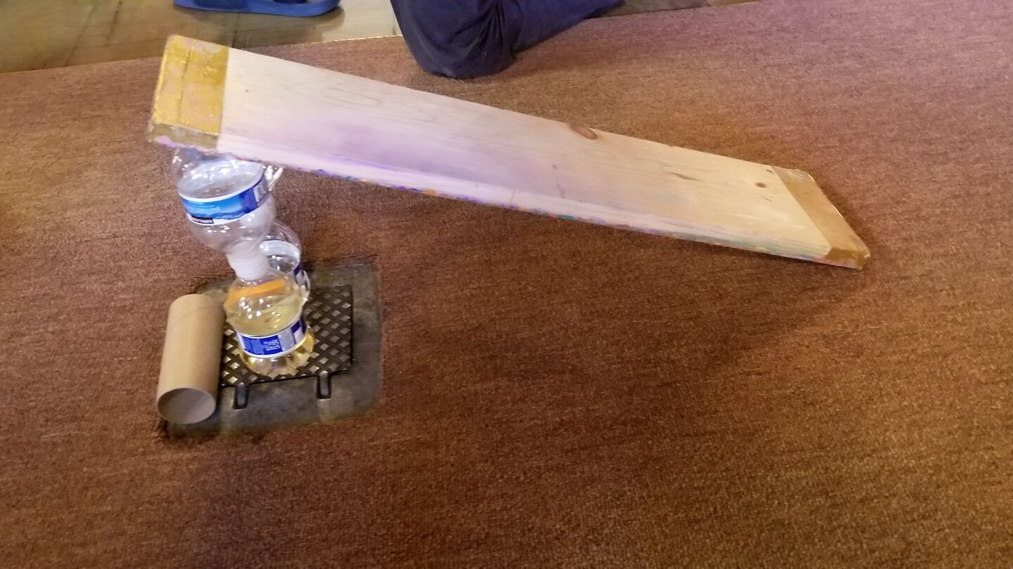 A small ramp on a carpet made out of a wood slat and propped up with two small water bottles