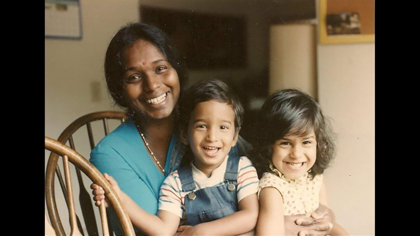 A woman sits hugging a little boy and girl.