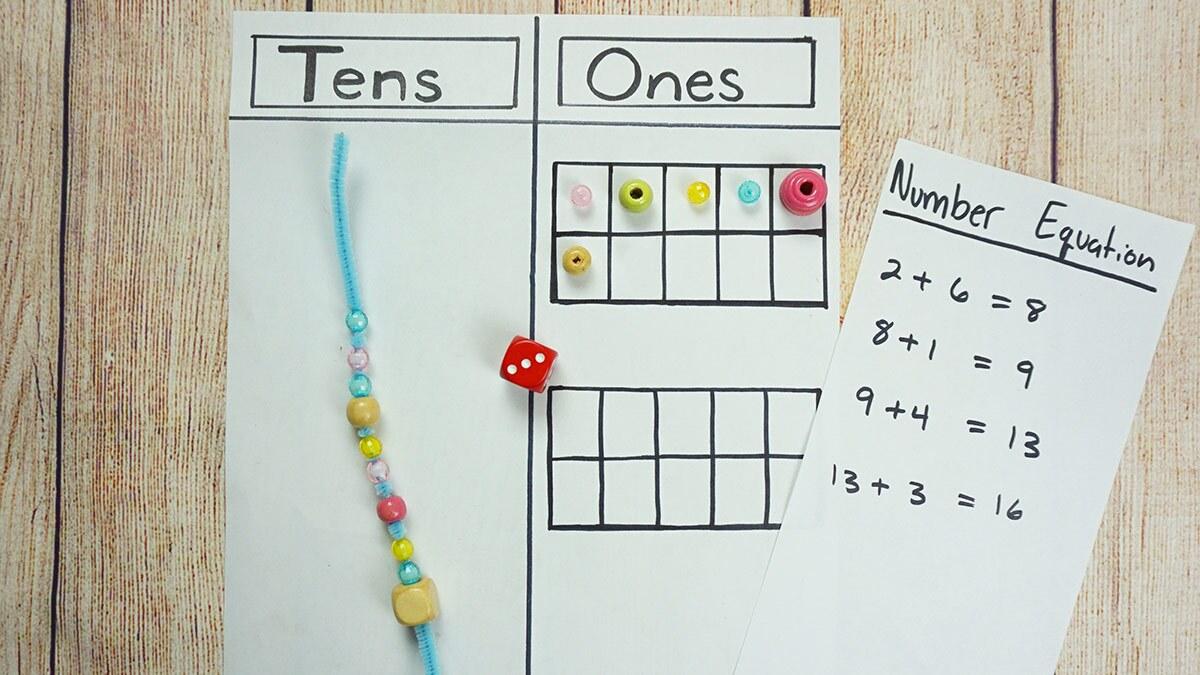 """Una hoja de papel dividida en dos columnas con los títulos """"decenas"""" y """"unidades"""" con cuentitas, limpiapipas, trozos de hilo y un marcador encima. Todo se coloca junto a una pequeña hoja con ecuaciones simples."""