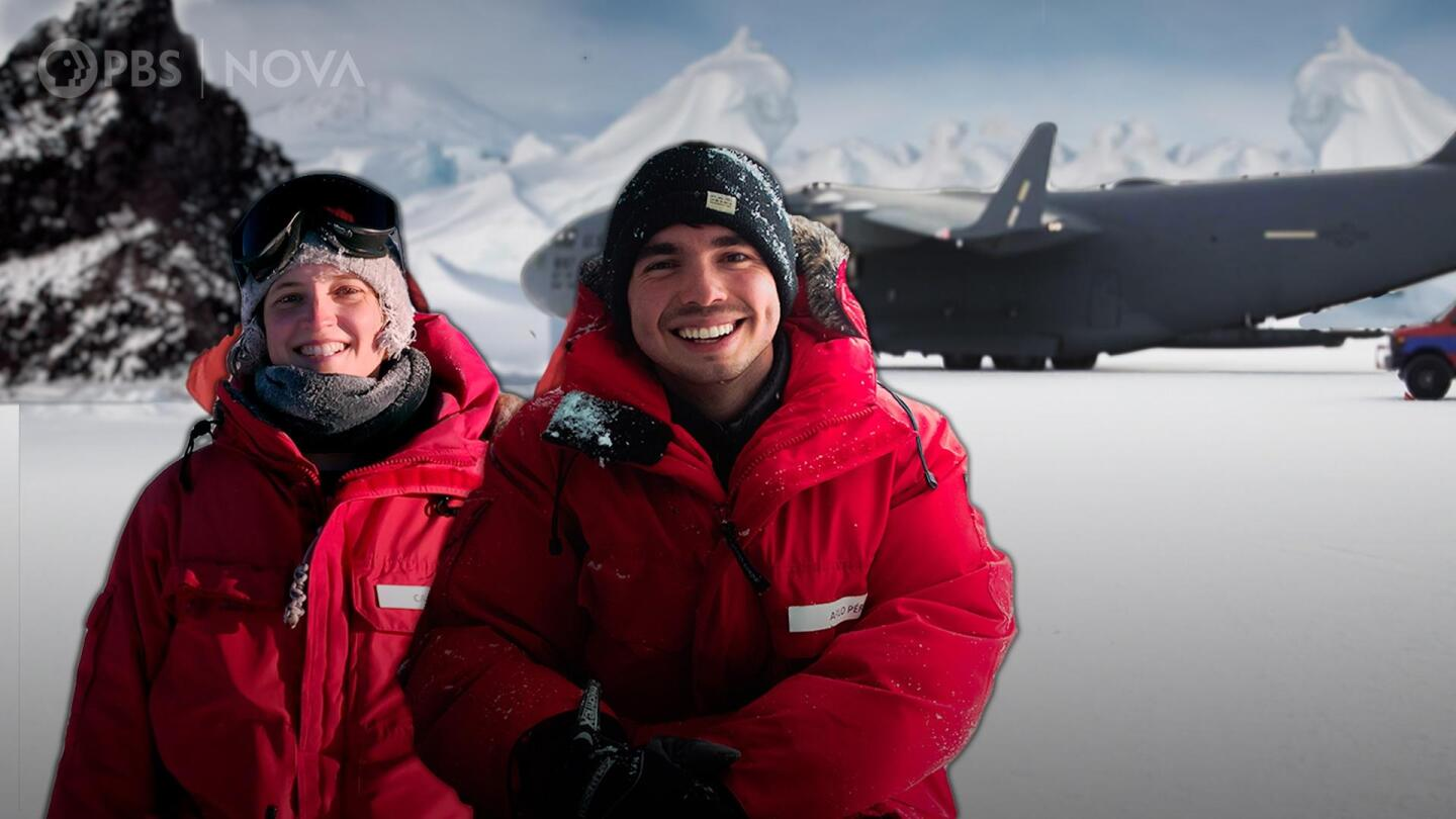 Two people wearing bright red winter coats smile.
