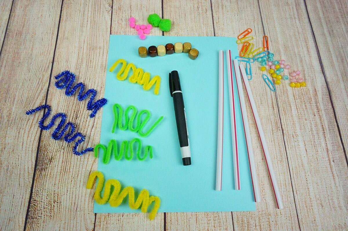 A wooden table with a piece of paper, a marker and small items arranged on top of it.