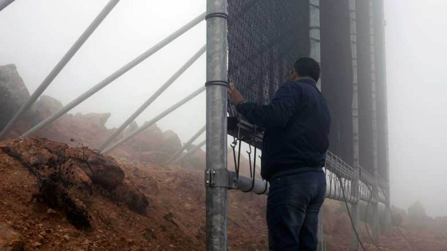 Man standing next to fog catcher in Morocco. | Nicky Milne/Thomson Reuters Foundation