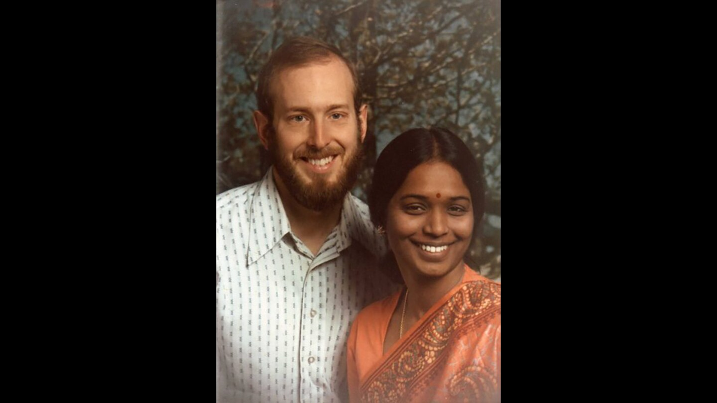 A woman in a sari with a bearded man, both smiling