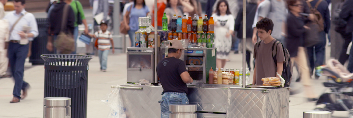 "A young customer waits for his order at a hot dog stand on a busy street. | Still from ""City Rising: Informal Economy"""