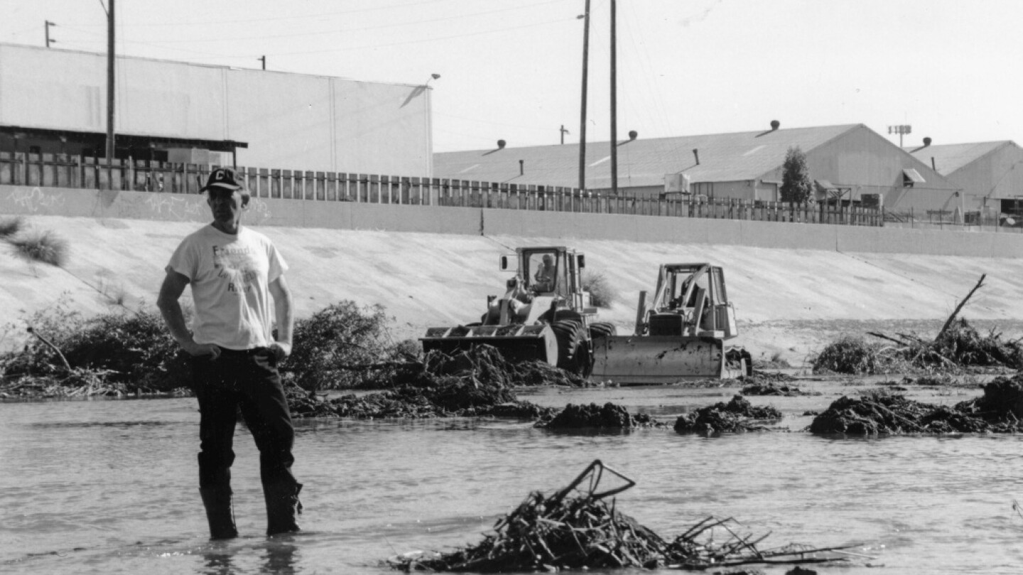 Lewis MacAdams, founder of Friends of the Los Angeles River, stands in the river as bulldozers clear vegetation from its channel in anticipation of heavy El Nino-driven rains, expected in the winter of 1997-98 | Blake Gumprecht, courtesy of FoLAR