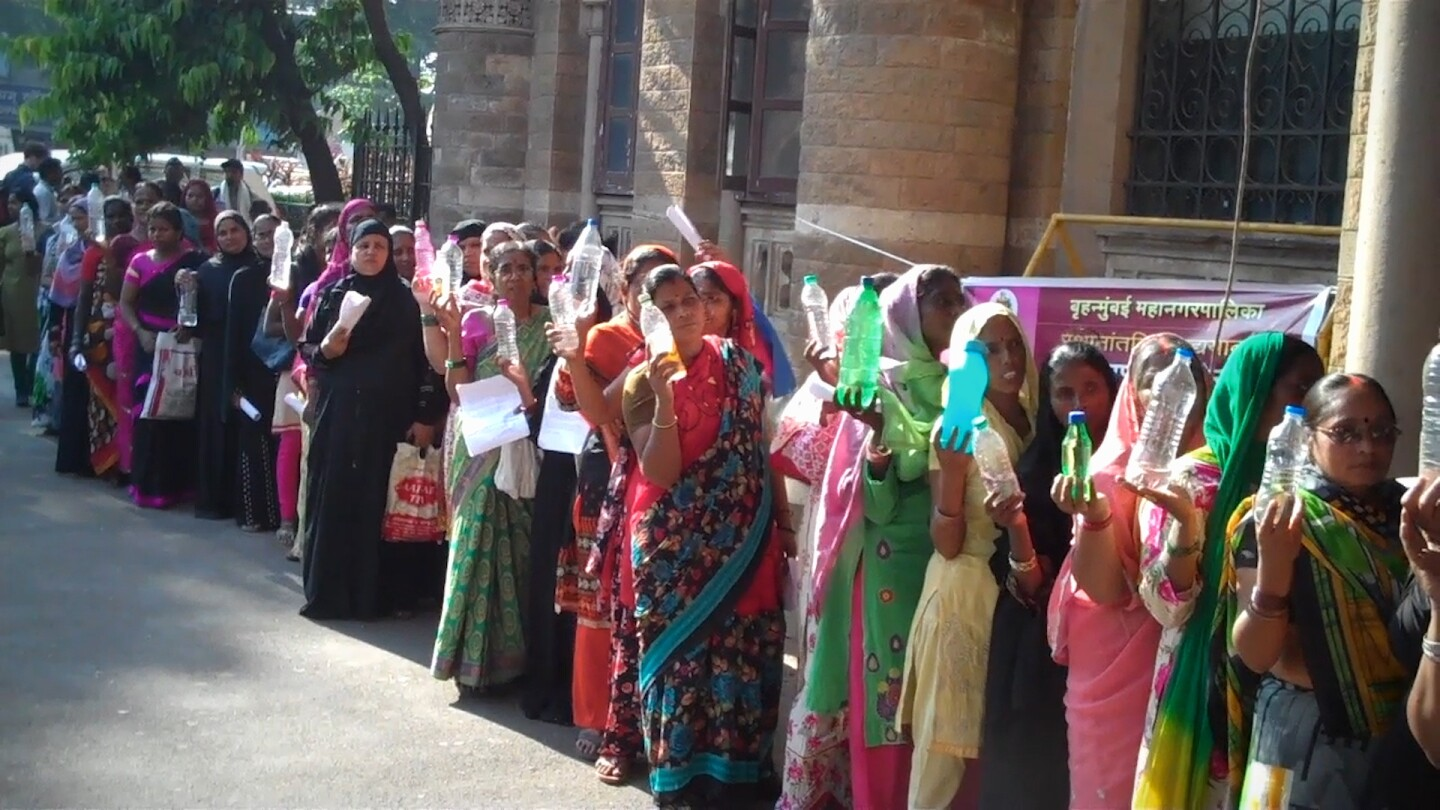 "Women in Mumbai line up to present local government officials examples of bad drinking water from their homes. | Still from ""Global Mosaic"""
