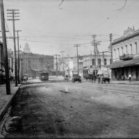 """An image of the French district in downtown Los Angeles. The image shows Aliso Street in downtown Los Angeles, California, with signs labeling buildings """"Griffins Transfer and Storage Co."""" and """"Cafe des Alpes"""" next to """"Eden Hotel,"""" which are located on opposite corners of Aliso and Alameda Streets. A Pacific Electric streetcar sign reads """"Sierra Madre"""" and automobiles and horse-drawn wagons are seen in the dirt road."""