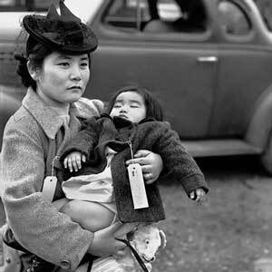 Fumiko Hayashida, 31, carries her daughter, Natalie Kayo, 13 months, as she prepares to board the ferry at Bainbridge Island, Washington.   Post-Intelligencer Collection, Museum of History & Industry