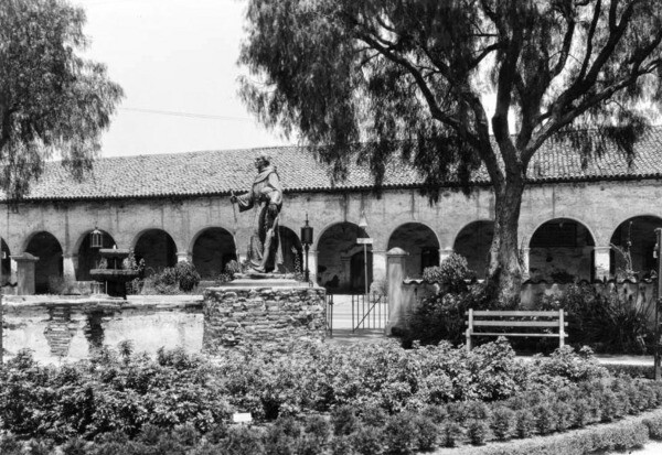 A pepper tree stands near a statue of a missionary at the San Fernando Mission. Courtesy of the USC Libraries - California Historical Society Collection.