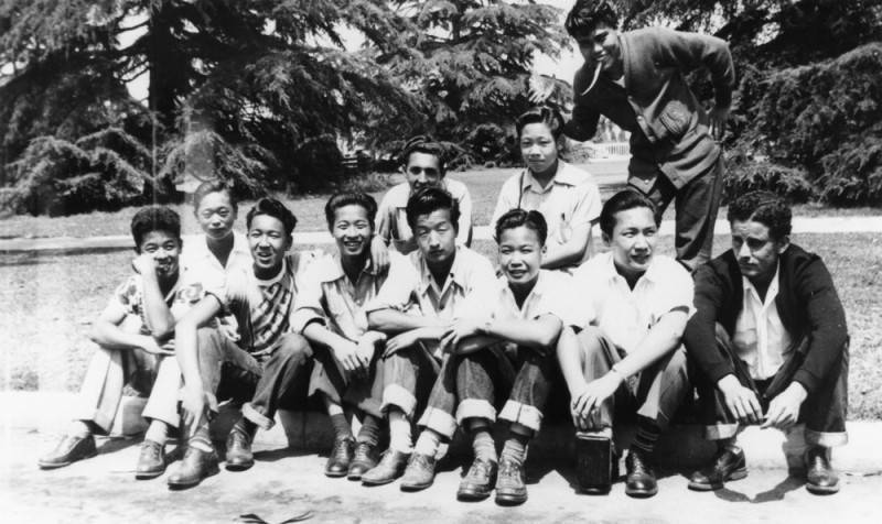 Black and white photo of several Japanese American boys sitting together in two rows, facing the camera