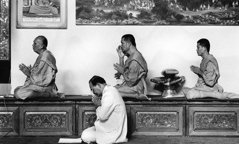 Black and white photo of four men praying at a Buddhist temple