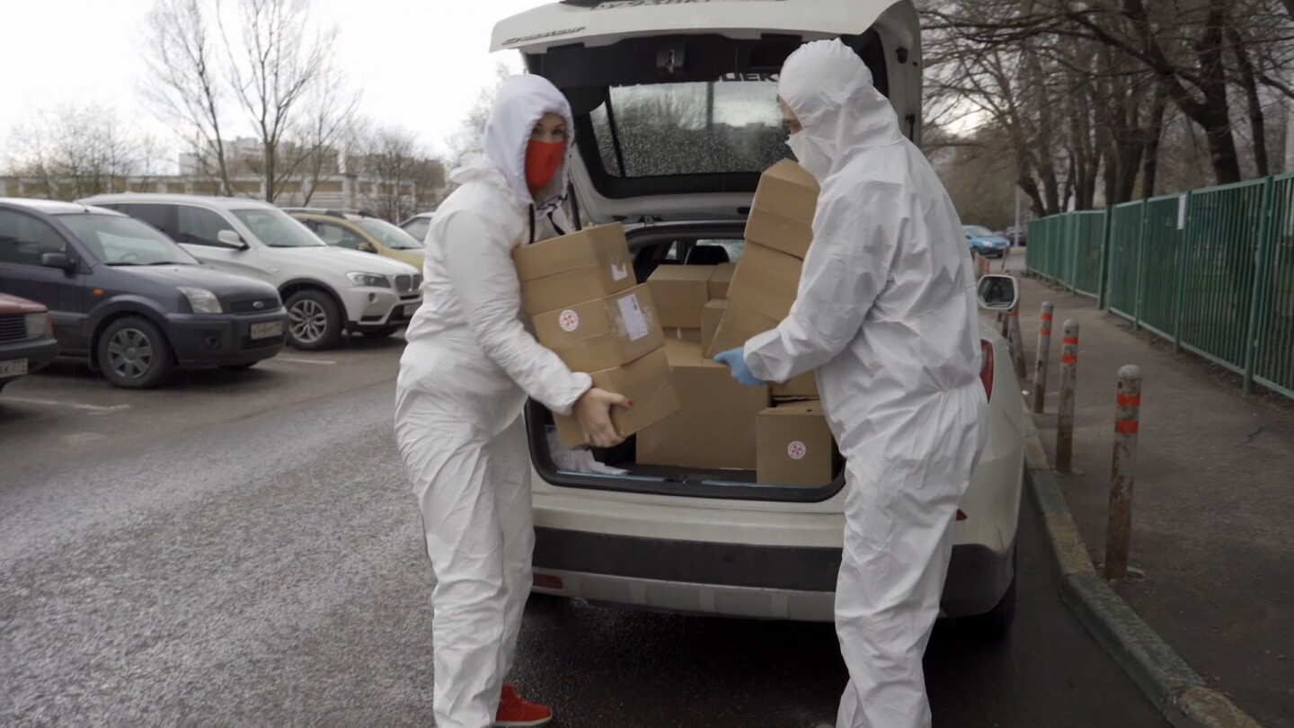 "Health workers lift boxes from the trunk of a car. | From ""Foreign Correspondent: The Doctor Vs The President"""
